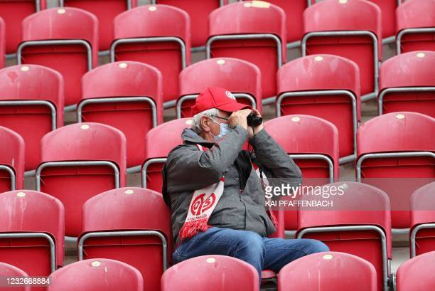 Lonely Mainz' supporter watches through binoculars sitting in the standsamong empty seats prior to the start of the German first division Bundesliga...
