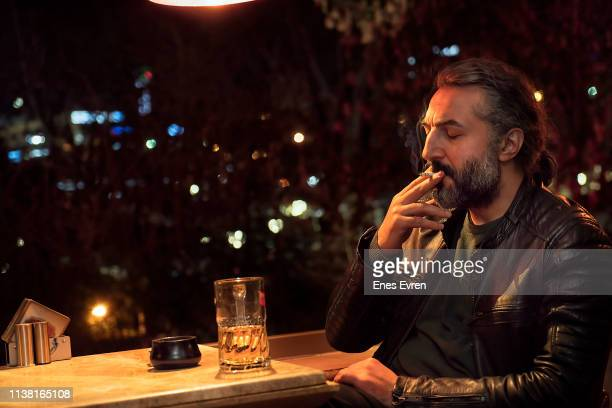 lonely man drinking beer, smoking cigarette in pub - after work stock pictures, royalty-free photos & images