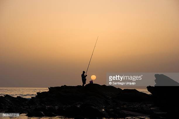 lonely man fishing at sunset - rocky coastline stock pictures, royalty-free photos & images