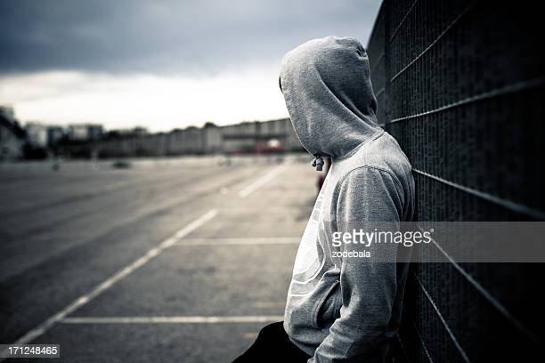 lonely man leaning on a fence - jonge mannen stockfoto's en -beelden