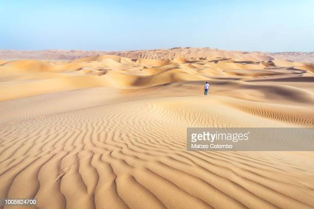 Lonely man on sand dune in the desert of Abu Dhabi