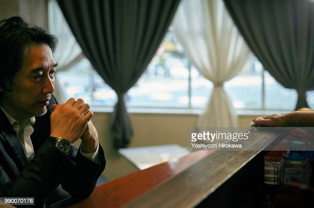 Lonely man seated silent at bar counter with bartender