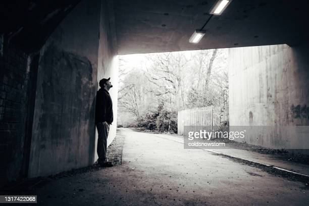 lonely man standing against wall in urban tunnel - hands in pockets stock pictures, royalty-free photos & images