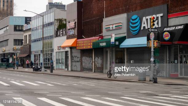 lonely man wearing a protective mask standing on delancey street in chinatown in front of the stores closed due to the covid-19 outbreak - alex potemkin coronavirus stock pictures, royalty-free photos & images