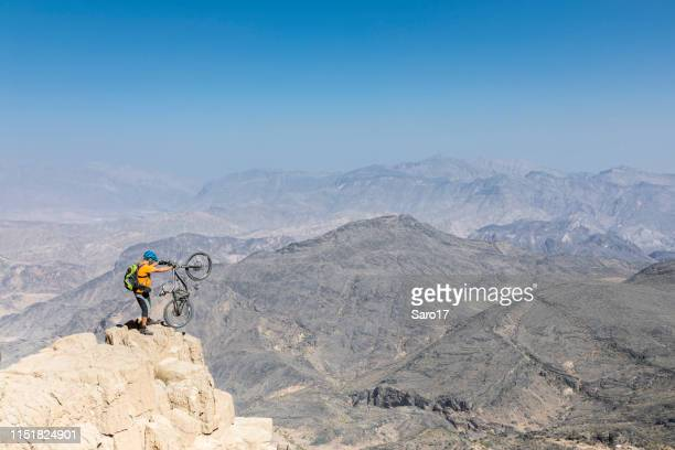 lonely mountainbiker is posing at hajar mountains, oman. - muscat governorate stock pictures, royalty-free photos & images