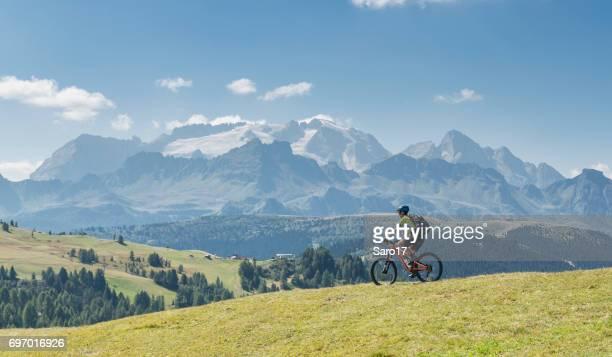 a lonely mountainbiker riding in front of mt. marmolada, italy - dolomiti foto e immagini stock