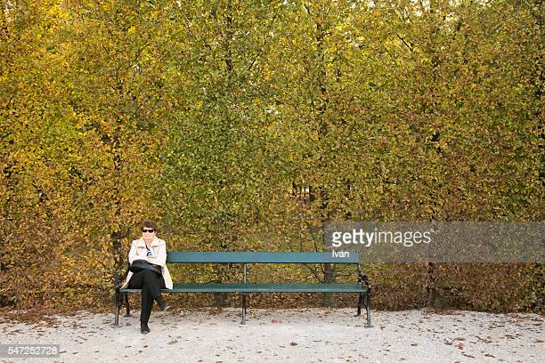 A Lonely Old Woman Wearing Sunglasses,  Sitting on a Bench in Front of Green and Yellow Leaf Wall