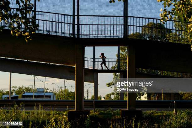 Lonely person runs along the pedestrian bridge as night falls. All kinds of physical activities usually popular among the Firmat's population, have...