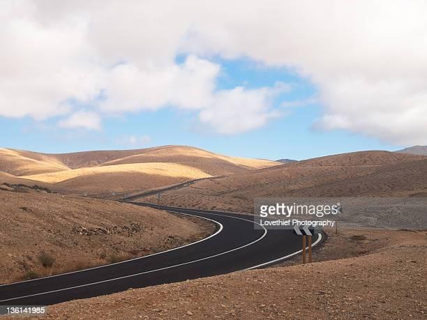 lonely road near pajara - hügelkette stock-fotos und bilder