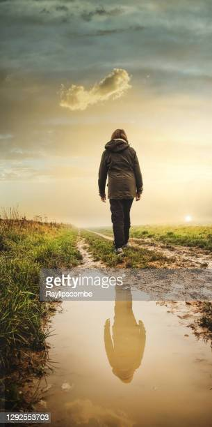 lonely sad woman walking along a long an endless muddy farm track vanishing into the distant horizon in the cotswold landscape as she reflects on life. - temperature stock pictures, royalty-free photos & images