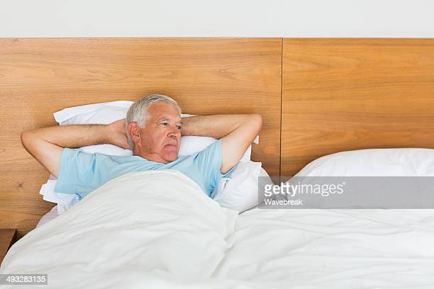 lonely senior man lying in bed - hands behind head stock pictures, royalty-free photos & images