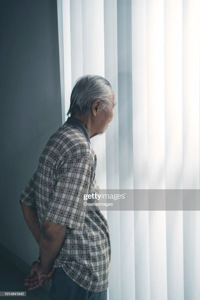 Lonely senior man standing by the window : Stock Photo