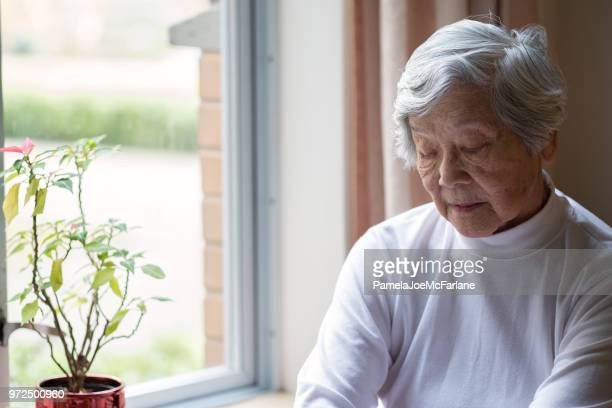 lonely, senior woman sitting by window with eyes closed - dementia stock pictures, royalty-free photos & images