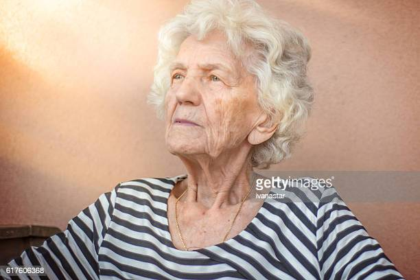 lonely senior woman sitting outdoors - grimassen stockfoto's en -beelden