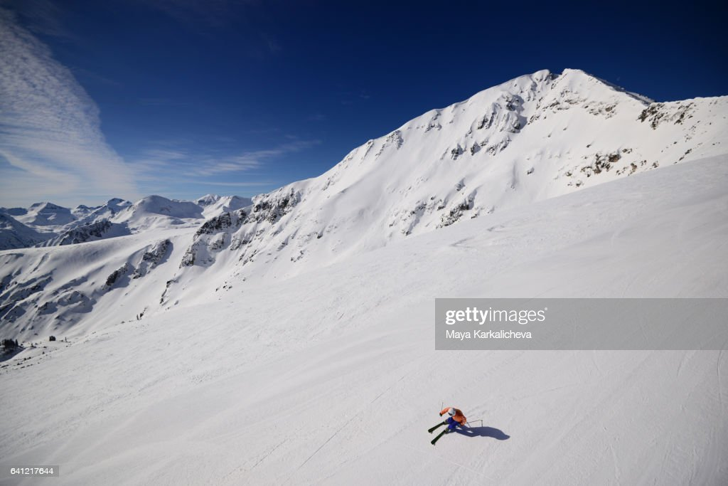 Lonely skier going down a ski slope : Stock Photo