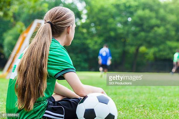 Lonely teenage soccer player sits on the sidelines