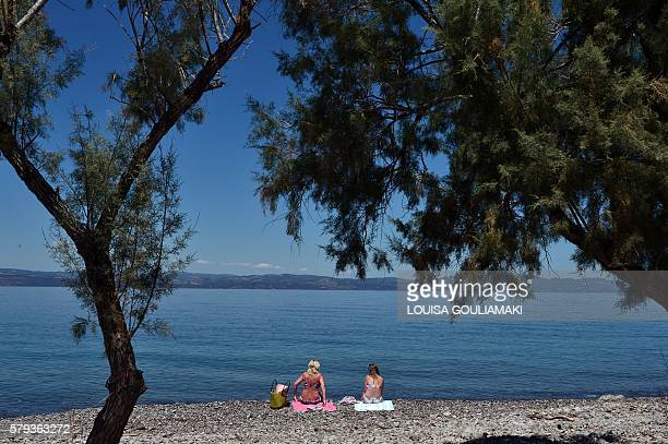 lonely tourists sit on the beach at Skala Sykamias on the island of Lesbos on July 21 2016 When a sea of humanity landed on their island's rocky...