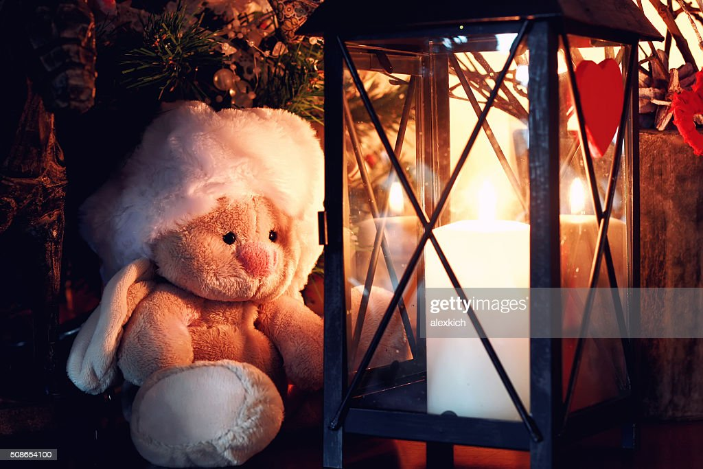 lonely toy near candle lamp : Stock Photo