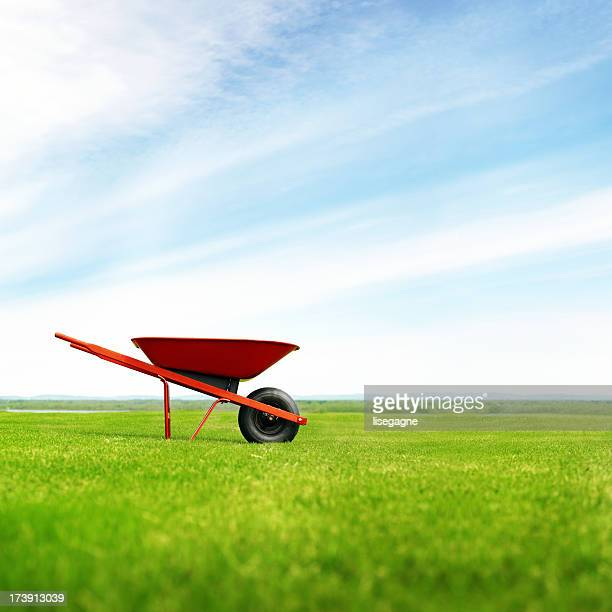 lonely wheelbarrow in the meadow - wheelbarrow stock photos and pictures