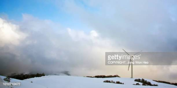 a lonely wind turbine on the mountain top in winter - gangwon province stock pictures, royalty-free photos & images