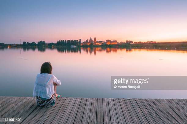 lonely woman admiring mantua reflecting in the mincio river at sunset, italy - flussufer stock-fotos und bilder