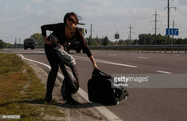 A lonely woman carrying her belongings tryies to stop military tvehicles to leave the site Ammunition depots in the town of Kalynivka in Vinnytsia...