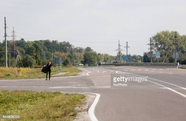 A lonely woman carrying her belongings walks follow the empty road from Kalynivka to leave the town Ammunition depots in the town of Kalynivka in...