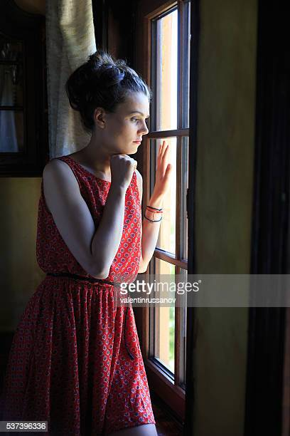 Lonely woman looking through the window