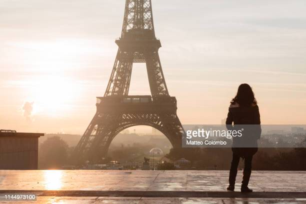 lonely woman standing in front of the eiffel tower, paris - esplanade du trocadero stock pictures, royalty-free photos & images