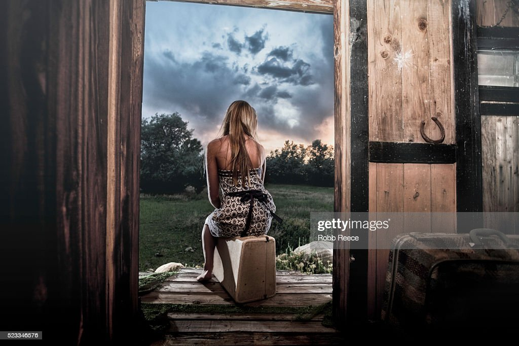 A lonely woman waiting on her porch ready to leave with luggage : Stock Photo