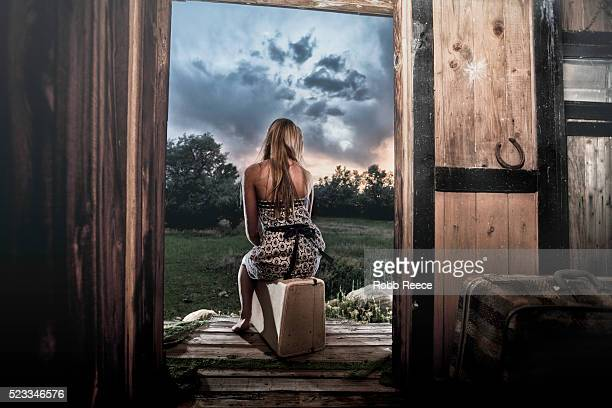 a lonely woman waiting on her porch ready to leave with luggage - robb reece 個照片及圖片檔