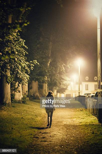 Lonely woman walking alone on path