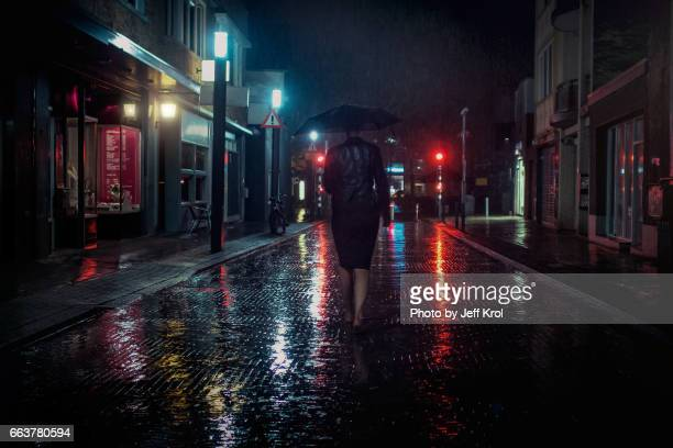 Lonely woman walking in the streets in the night, rainy day, covered with an umbrella in a cinematic scene.