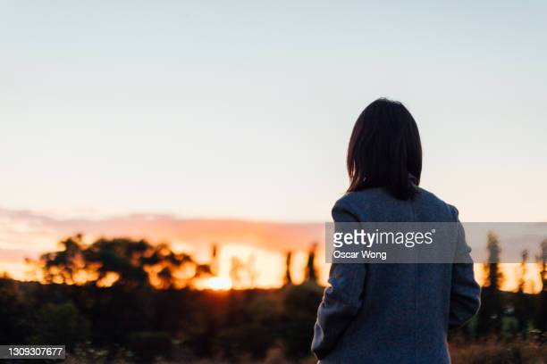 lonely woman watching sunset - dramatic sky stock pictures, royalty-free photos & images