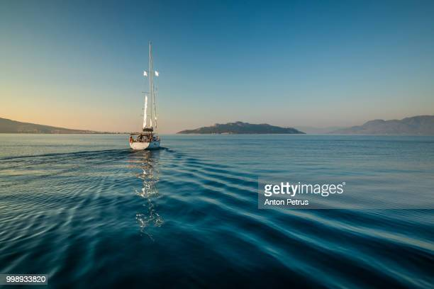 lonely yacht sailing on silent sea. aegina island, greece - yacht foto e immagini stock