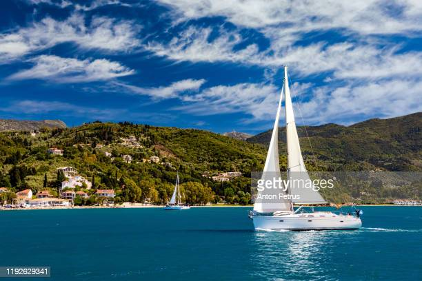 lonely yacht with white sails in the sea on a background of beautiful clouds. summer vacation - sailing stock pictures, royalty-free photos & images