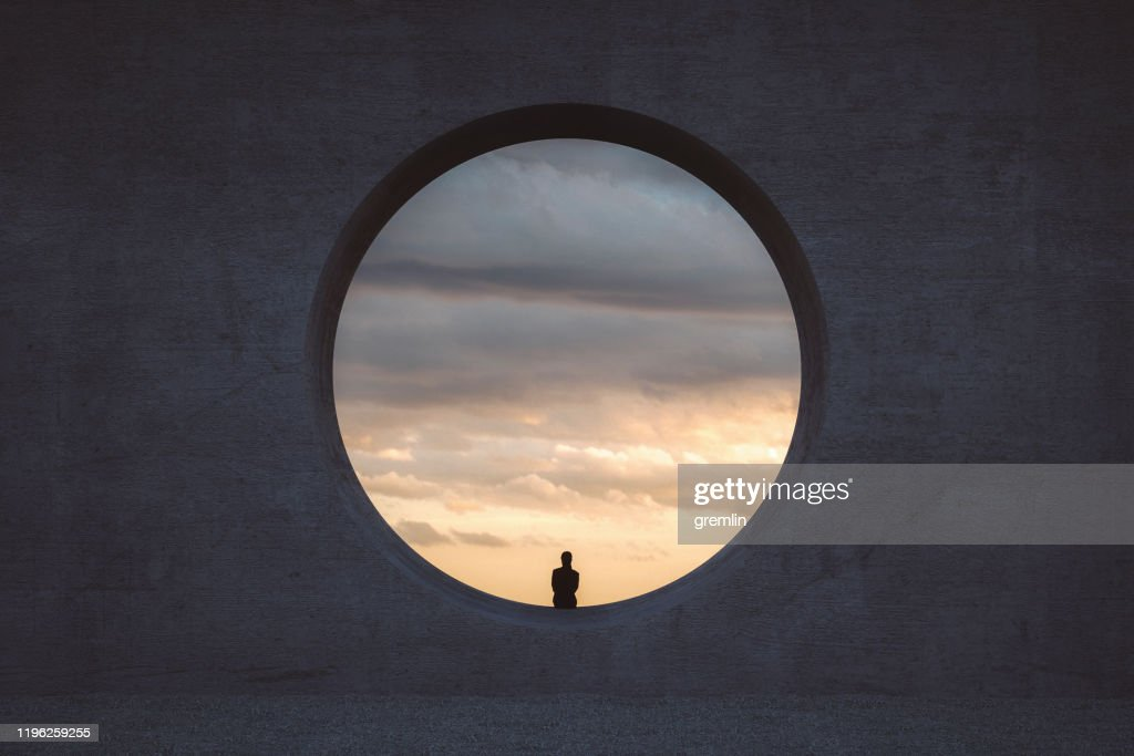 Lonely young woman looking through concrete window : Foto stock