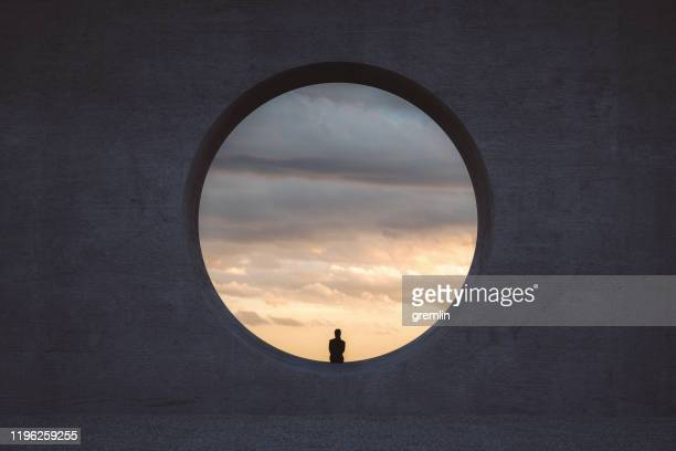 lonely young woman looking through concrete window - architecture stock pictures, royalty-free photos & images