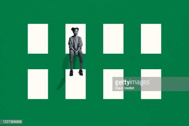 lonely young woman sitting on green grid window - eenzaamheid stockfoto's en -beelden