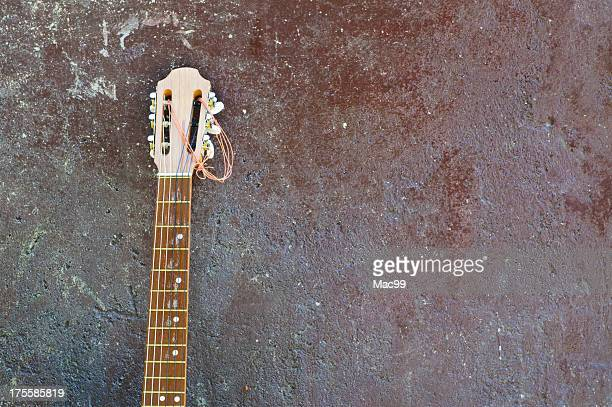 Lonesome guitar leaning on wall