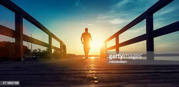 Homme solitaire vacances marchant sur un ponton au coucher du soleil