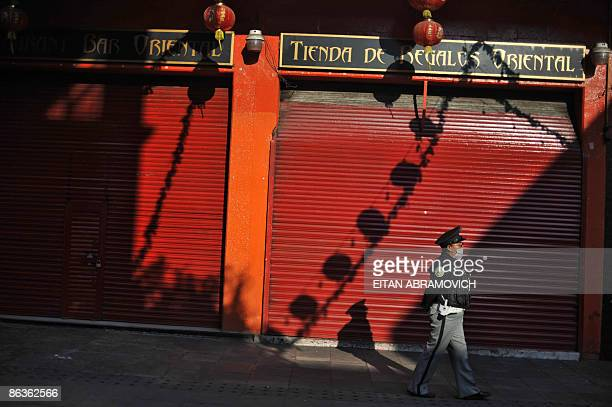 A lonesome policewoman wearing a face mask patrols along Mexico's City Chinatown on May 3 as all stores remain closed The influenza A virus epidemic...