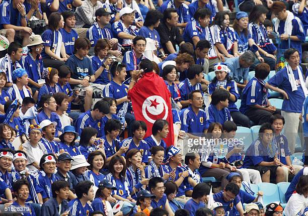 A lonesome supporter of the Tunisian team walks wrapped in the national colors through a sea of Japanese fans crowding the bleechers of Osaka Nagai...