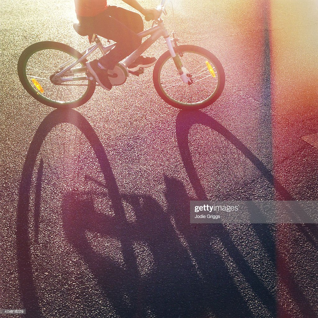 Long afternoon shadow of child riding bicycle : Stock Photo