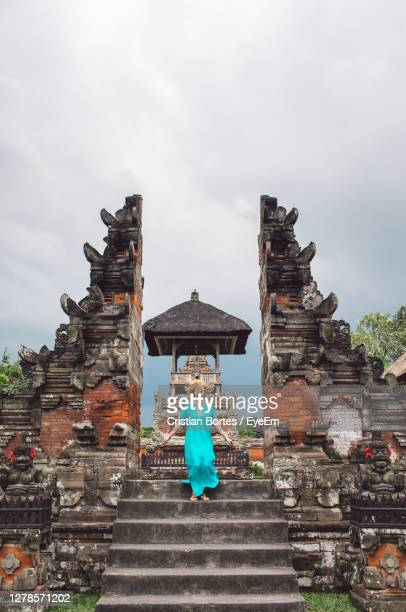 long angle view of woman standing on a stairs in front of a temple gate - bortes stock-fotos und bilder