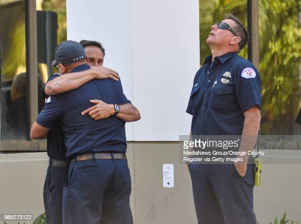 Long Beach firefighters console each other outside St Mary Medical Center after Long Beach Fire Department Capt Dave Rosa was shot and killed...
