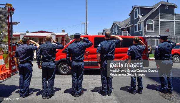 Long Beach firefighters salute as a van carrying the family of Long Beach Fire Department Capt Dave Rosa leaves St Mary Medical Center after his body...