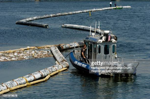 Long Beach Police boat sits near the spot where a body is wedged in a trash boom at the mouth of the Los Angeles River on Wednesday, MArch 15, 2006.