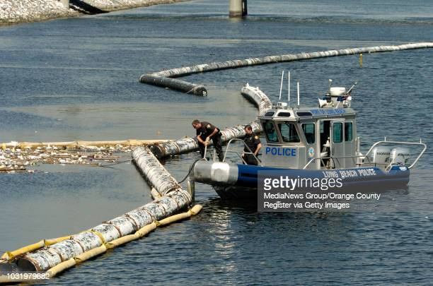 Long Beach Police officer examine a trash boom at the mouth of the Los Angeles River where a body was found on Wednesday, MArch 15, 2006. The body is...