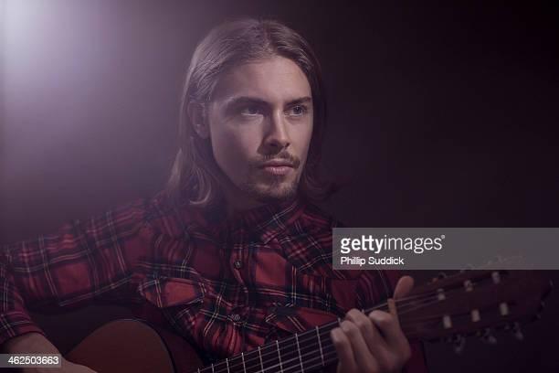 long blonde hair goatee beard man playing guitar